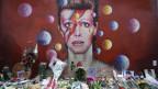 David Bowie auf eine Wand gemalt, davor zig Blumensträusse.