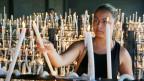 Symbolbild: eine Frau zündet eine Kerze in der Kirche an.