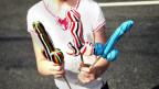 Jemand hält ein paar Dildo-geformte Lollipops in der Hand.
