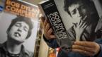 Ein Mann liest ein Bob Dylan Lyrikband.