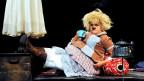 Eine Frau, die als Clownin verkleidet ist, auf der Bühne