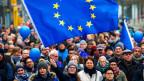 Friedliche Menschenmenge, ganz vorne ein Mädchen, das die Europafahne schwingt.