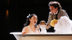 Operninszenierung: Eine Darstellerin sitzt in einer Badewanne, die andere hält ihr eine Stoffpuppe hin und hält einen Waschschwamm in der anderen Hand.