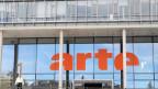 Das Emblem von Arte in Orange auf einem Glashaus