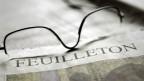 Eine Zeitung mit der Aufschrift «Feuilleton», auf ihr liegt eine Brille