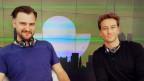 Zwei Männer sitzen vor Radiomikrofonen an einem Tisch.