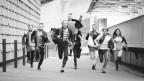 Ein Dutzend junger, rebellisch gekleideter Menschen rennt euphorisch und mit grossen Schritten auf die Kamera zu