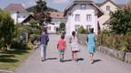 Vier Kinder von hinten, die durch ein schweizer Dorf laufen