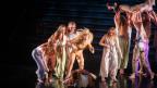Junge Frauen mit wehenden Haaren und Kleidern performen auf einer Bühne