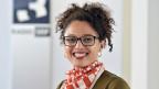 Eine Frau mit Brille und dunklen lockigen Haaren lacht in die Kamera