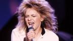 Die Sängerin mit langen blonden Haaren und Jacket singt in ein Mikrofon
