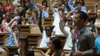 Jugendliche sitzen im Nationalratsaal und heben die Hand zur Abstimmung