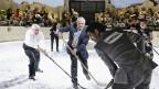 Männer in Anzügen spielen in einer Arena Eishockey, einer trägt die Aufschrift «Companies» am Rücken