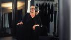Frau in schwarz mit kurzen grauen Haaren und Brille hockt auf dem Boden einer Modeboutique und schaut streng in die Kamera