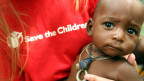 Eine Mitarbeiterin von Save the Children mit einem Kind.
