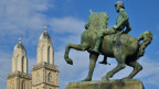 Statue eines Reiters auf einem Pferd, im Hintergrund der Grossmünster von Zürich