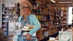 Eine Frau mit Brille und vielen Büchern in der Hand steht lächelnd in einer Buchhandlung.
