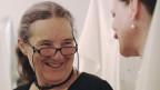 Frau mit Brille und scharzem Shirt schaut eine Person von der Seite an. Sie hat lange graue Haare.