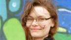 Frau mit rötlich-braunen langen Haaren, lächelt mit geschlossenem Mund in eine Kamera. Sie trägt eine leichte Brille mit dunkelbraunem Rahmen.