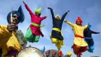 Indische Männer in farbigen Gewändern springen in die Luft.