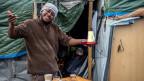 Ein Flüchtling in Calais. Er lacht.