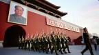 Eine Militäreinheit marschiert unterm dem Bildnis Maos.
