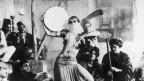 Ein Schwarz-Weiss-Foto von einer orientalischen Frau, die in einem Kreis von musizierenden Männern einen Bauchtanz vorführt.
