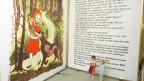 Zwei Kinder stehen vor einem riesengrossen Märchenbuch.