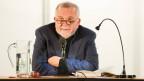 Ein freundlicher Herr mit Brille und Bart an einem Rednerpult mit Mikrofon