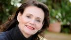Frau mit langen, dunklen Haaren und roten Lippen schaut in die Kamera und lächelt.