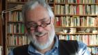 Ein Mann mit Brille vor Büchergestell blickt in die Kamera