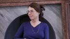 Frau mit langen braunen Haaren und grosser, organge-braunenen Hornbrille sitzt in einem Sessel, spricht und gestikuliert.