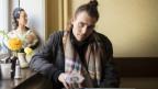 Mann Mitte 30ig mit langen, braunen, zusammengebundenen Haaren sitzt an einem Tisch
