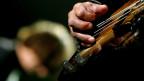 Nahaufnahme einer Hand, die auf einem Bass spielt