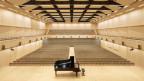 Ein heller, geräumiger Konzertsaal mit Konzertflügel im Vordergrund