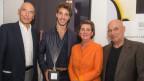 Der junge Preisträger, im Bild mit drei anderen Personen, hält einen Award in der Hand
