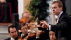 Junger Mann dirigiert andere Männer mit Violine