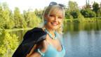 Eine blonde Frau steht vor einem Gewässer und lächelt in die Kamera