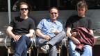 Drei Männer sitzen nebeneinander in einem Kaffee in der Sonne.