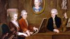 Mozart mit seiner Schwester am Klavier. Der Vater spielt Violine. An der Wand hängt ein Portrait der Ehefrau und Mutter.