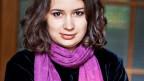 Porträt einer Frau mit pinkem Schal.