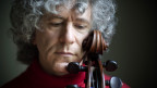 Ein Mann mit grauen Locken schaut gegen unten, an seiner Wange lehnt ein Cellobügel.