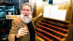 Organist Wolfgang Sieber sitzt vor einer Orgel.