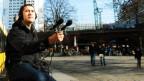 Ein Mann trägt Kopfhörer und hält ein Mikrofon in die Luft.