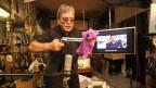 Ein Mann steht in einem Sammelsurium an Gegenständen vor einem Mikrofon und richtet eine Pistole auf ein pinkes Stofftier