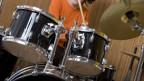 Bub spielt Schlagzeug.