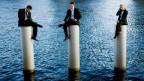 Drei Menschen sitzen erhöht, unter ihnen ist Wasser