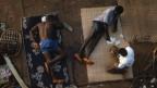 Vogelperspektive: Drei Männer sitzen auf dem Boden und spielen Karten