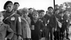 Kinder stehen in einer Reihe, schwarz-weiss