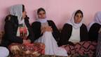 Drei Frauen mit leichtem Kopftuch um Hals und Kopf sitzen an einer rosafarbenen Wand.
